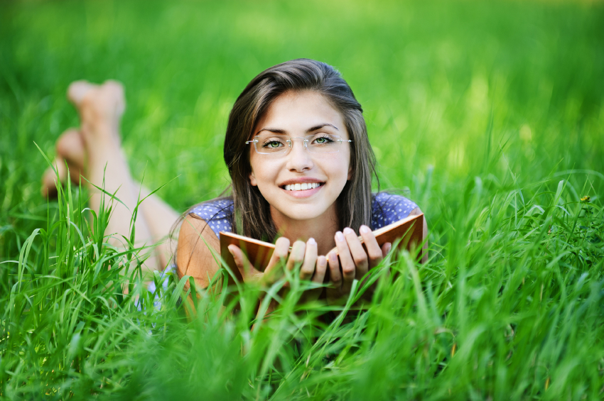 pretty young woman glasses lying reading book